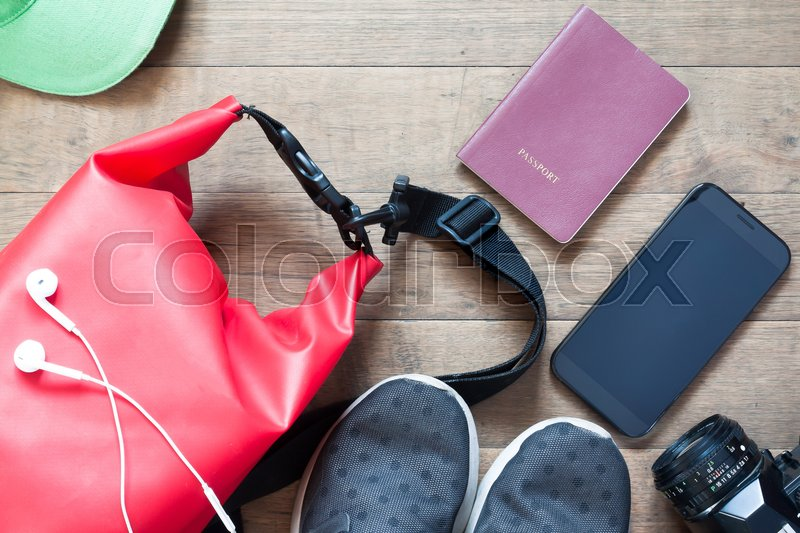 Stock image of 'Overhead shot of travel items and accessories with mobile device on wood background, flat lay of summer and vacation items'
