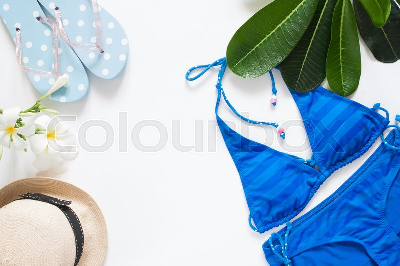 Overhead view of summer concept with blue stripe bikini, sandal, hat, iced drink and plumeria flower, Isolated on white background, stock photo