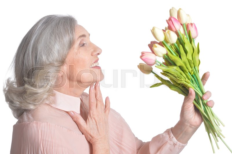 Stock image of 'Beautiful senior woman in pink blouse with bouquet of tulips isolated on white background'