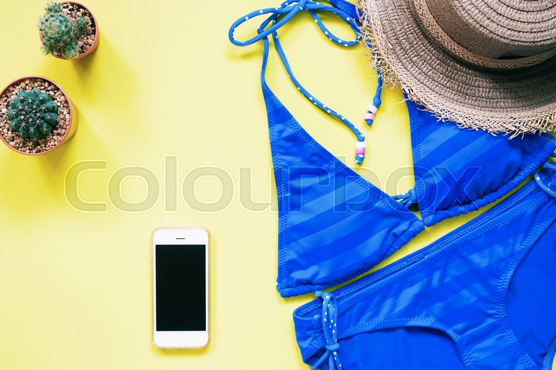 Stock image of 'Blue color swimwear with smartphone, cactus and hat flat lay on yellow background, Summer vacation concept'