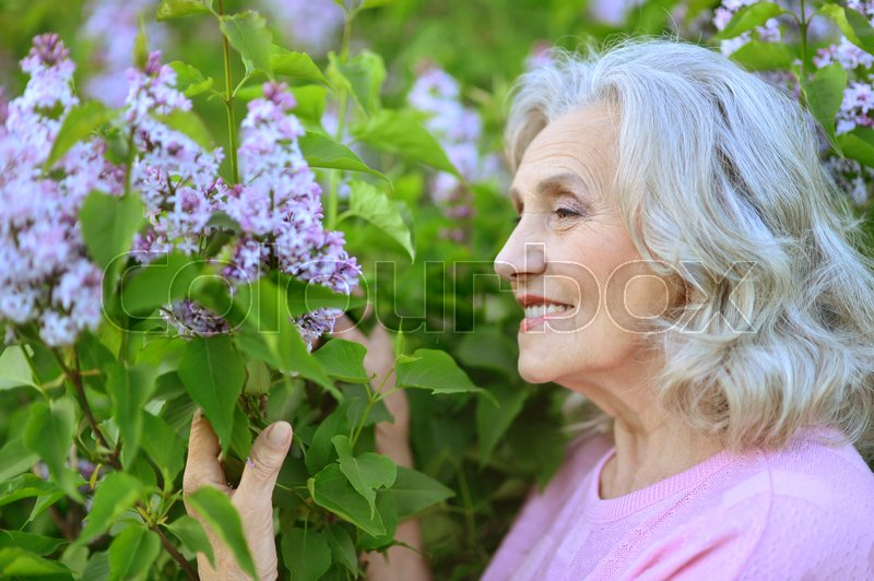 Stock image of 'beautiful senior woman standing near blooming tree'