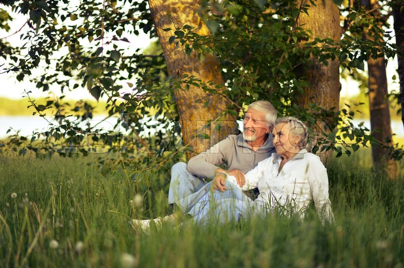 Stock image of 'happy senior couple sitting on green meadow'