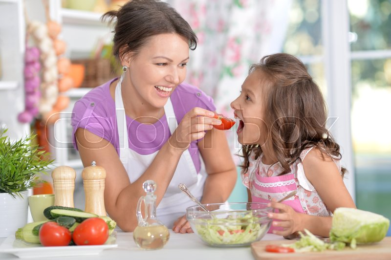 Stock image of 'Mother and daughter preparing dinner together on kitchen'