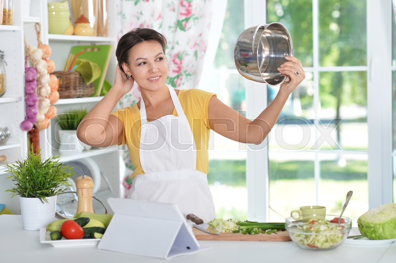 Stock image of 'Beautiful young woman in headphones preparing dinner on kitchen'