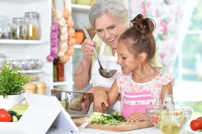 Stock image of 'grandmother and granddaughter preparing dinner on table with tablet'