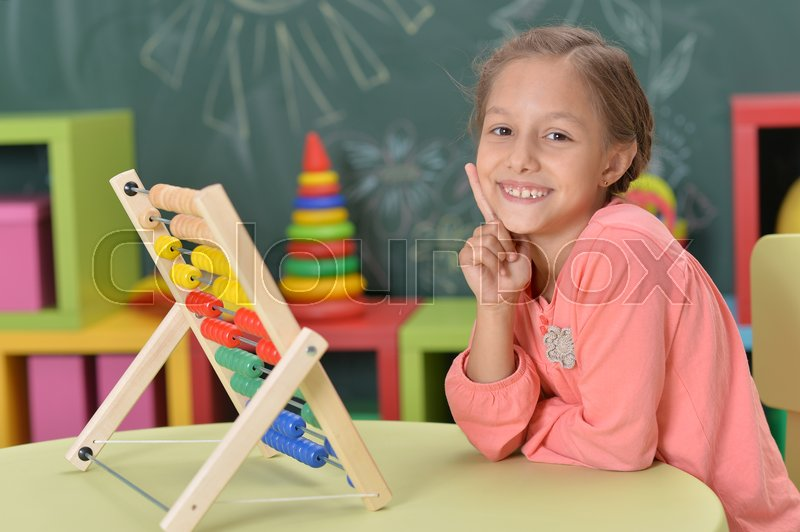 Stock image of 'Cute little girl learning to count on abacus'