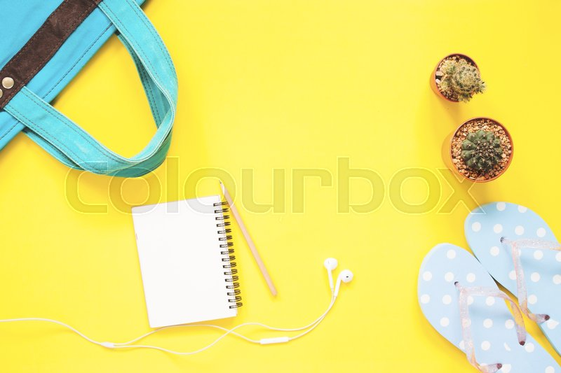 Stock image of 'Empty notebook, earphones, cactus with woman items on yellow background with copy space'