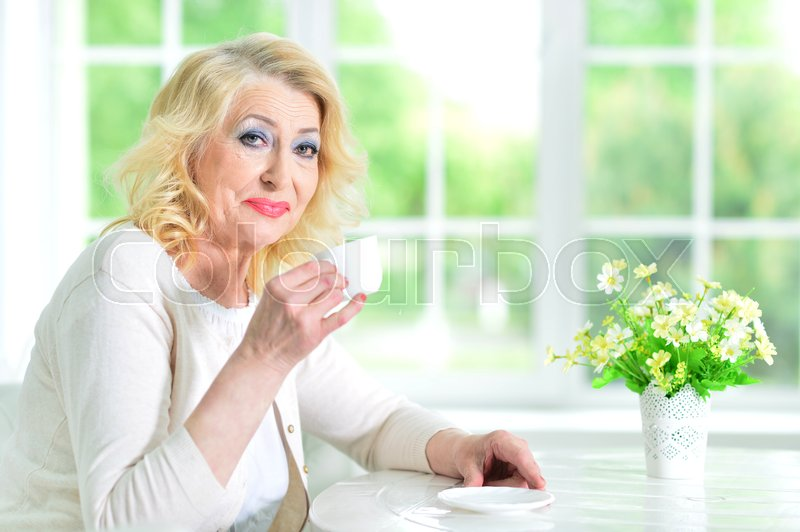Stock image of 'senior woman sitting at table with cup of tea'