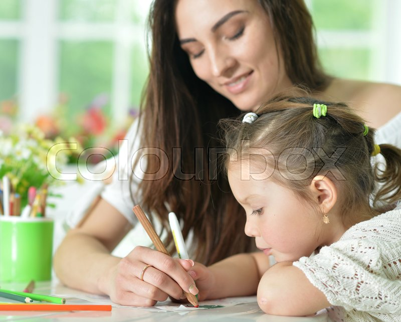 Stock image of 'Happy mother and her cute little daughter drawing with pencils together'
