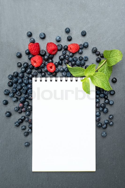 Stock image of 'Blueberries, raspberries, mint and notepad for writing notes or resolutions, concept of diet, slimming, detox, healthy lifestyles and nutrition. Mock up, space for text.'