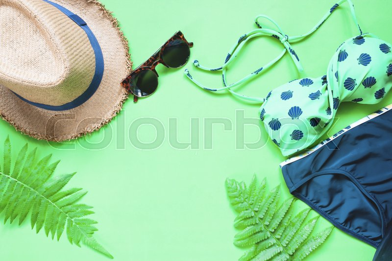Stock image of 'Flat lay of bikini and accessories with fern leaves on green background, Summer concept'