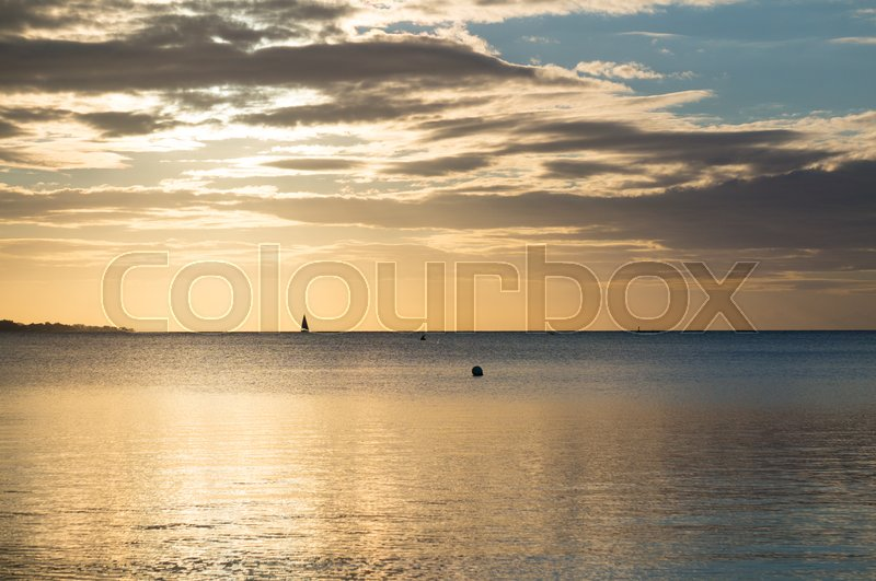 Stock image of 'Beautiful sunrise in the summer over silent glossy sea And clouds in the sky . Panorama'