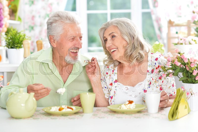 Stock image of 'Happy senior couple having breakfast together in kitchen'