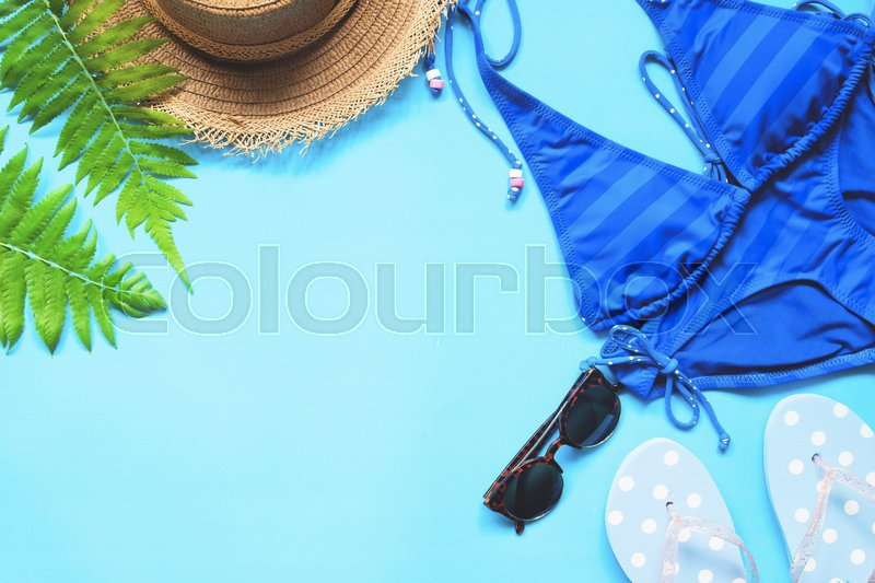 Stock image of 'Blue color bikini, sunglasses, hat and polka dot sandals on blue background, Flat lay summer collection'