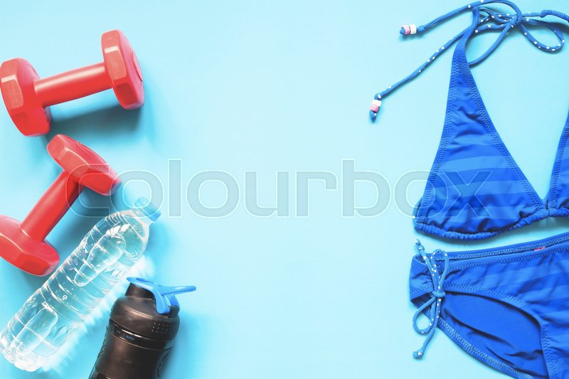 Stock image of 'Beauty concept with sport equipments and blue color bikini on blue background, Flat lay healthy concept'