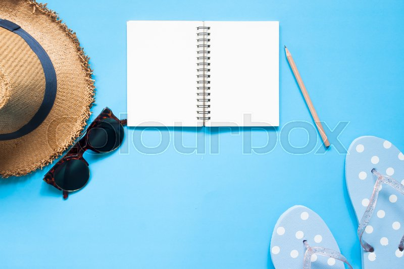 Stock image of 'Overhead view of empty notebook with pencil, hat, sunglasses and sandal on blue color background'