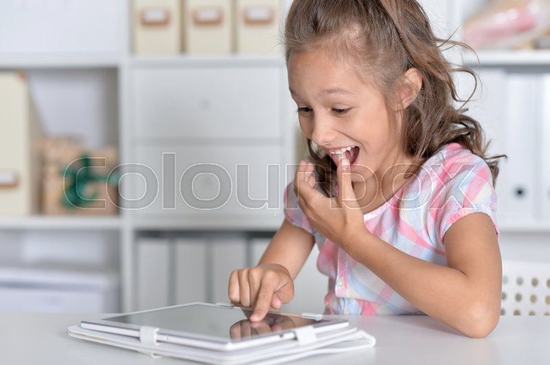 Stock image of 'Little girl sitting at table and using modern tablet'