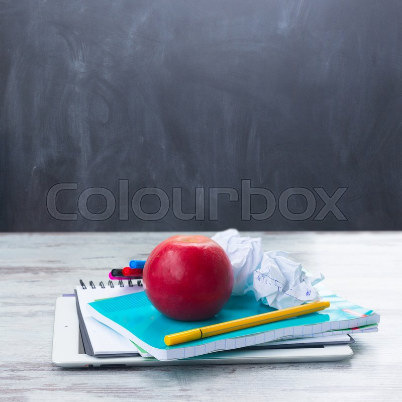 Stock image of 'Apple with school supplies on white wooden table, empty blackboard in background'