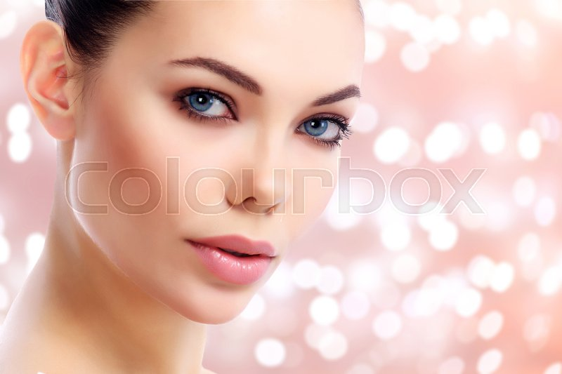 Stock image of 'Closeup shot of beautiful female face against an abstract background with blurred lights'