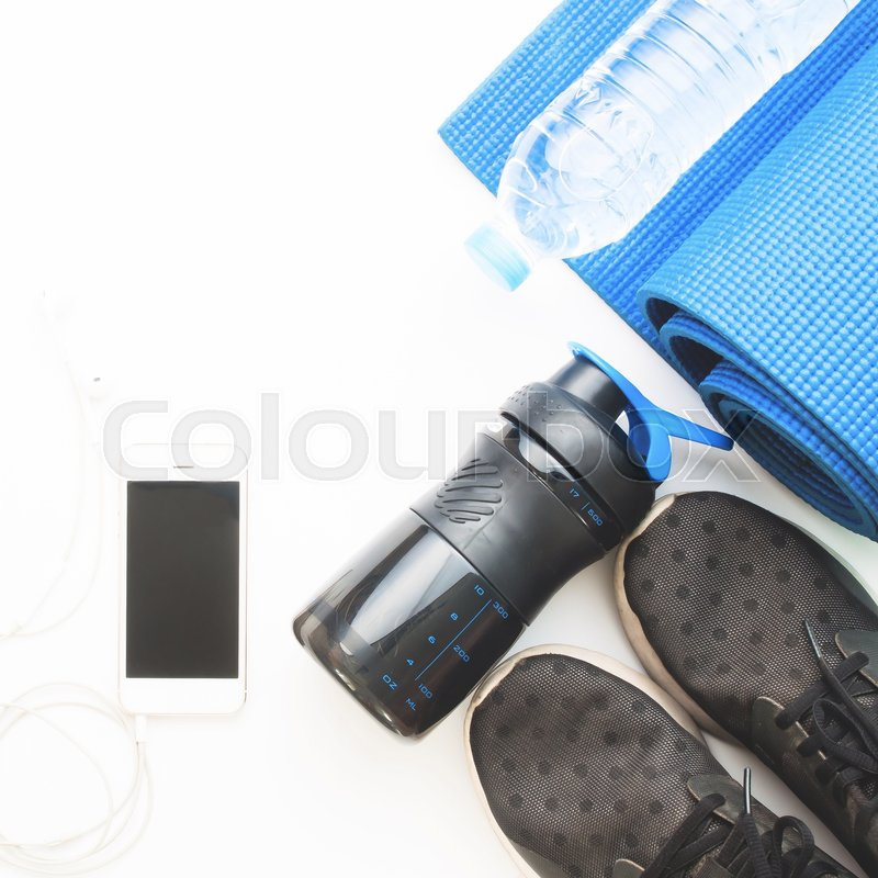 Stock image of 'Flat lay of cellphone with blue color yoga mat, bottle of water and black sneakers on white background, Working out and Healthy concept, Top view'