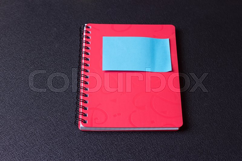 Stock image of 'Red notepad on a spiral with a sticker on a black background'