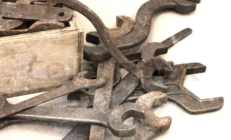 Stock image of 'Collection of old rusty wrenches on a dirty floor'
