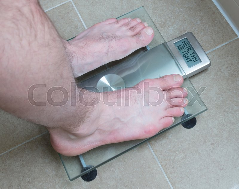 Stock image of 'Closeup of man's feet on weight scale - Healthy weight'