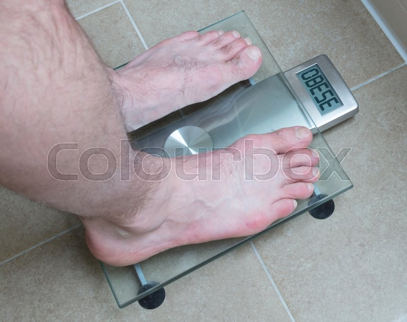 Stock image of 'Closeup of man's feet on weight scale - Obese'