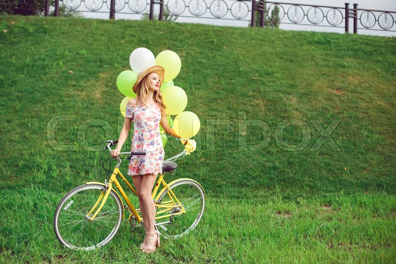 Stock image of 'Beautiful young woman on a bicycle on a green lawn background. Summer lifestyle and active rest. Yellow bicycle and balloons.'
