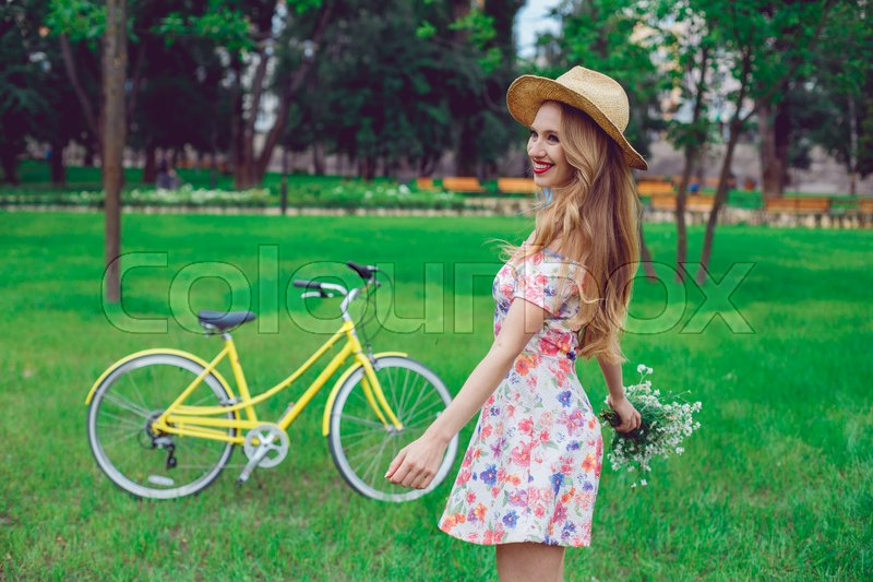 Stock image of 'Beautiful happy young woman enjoying summer with wild-flower bunch. Happy girl dancing outdoor, relaxation and good mood in park, sunset. Bicycle on the background.'