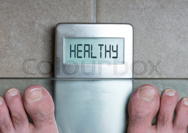 Stock image of 'Closeup of man's feet on weight scale - Healthy'