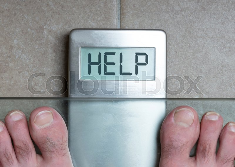 Stock image of 'Closeup of man's feet on weight scale - Help'