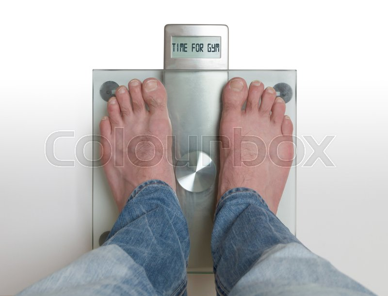 Stock image of 'Closeup of man's feet on weight scale - Time for gym'