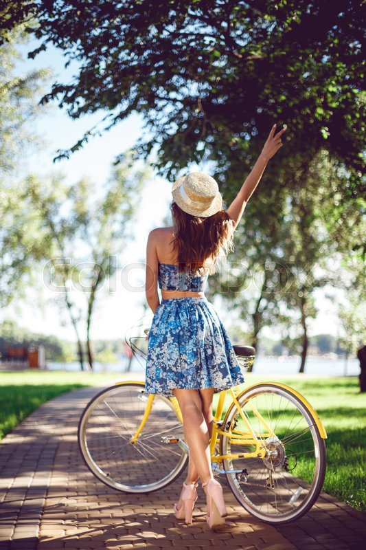 Stock image of 'View from the back of a beautiful young woman with a bicycle showing a victory sign. A woman bicycling posing with a yellow retro bicycle.'