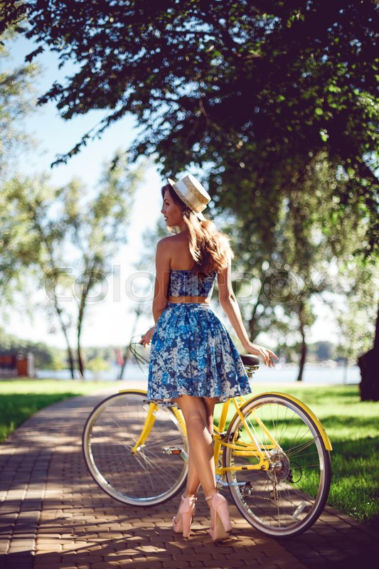 Stock image of 'View from the back woman bicycling posing with a yellow retro bicycle. Active lifestyle concept.'
