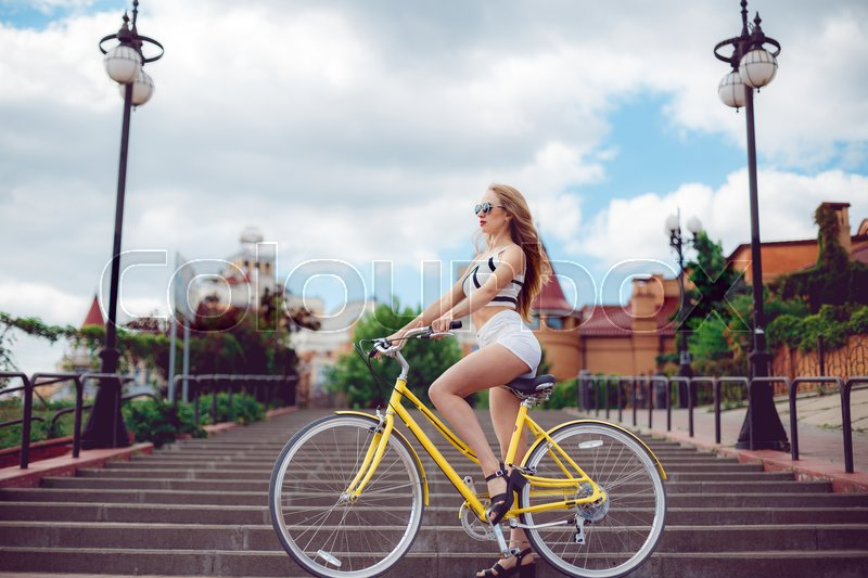 Stock image of 'Young beautiful hipster woman in white shorts, summer trend style near beach, riding bicycle. Active fashionable blonde woman riding a vintage bike on urban background at sunset.'
