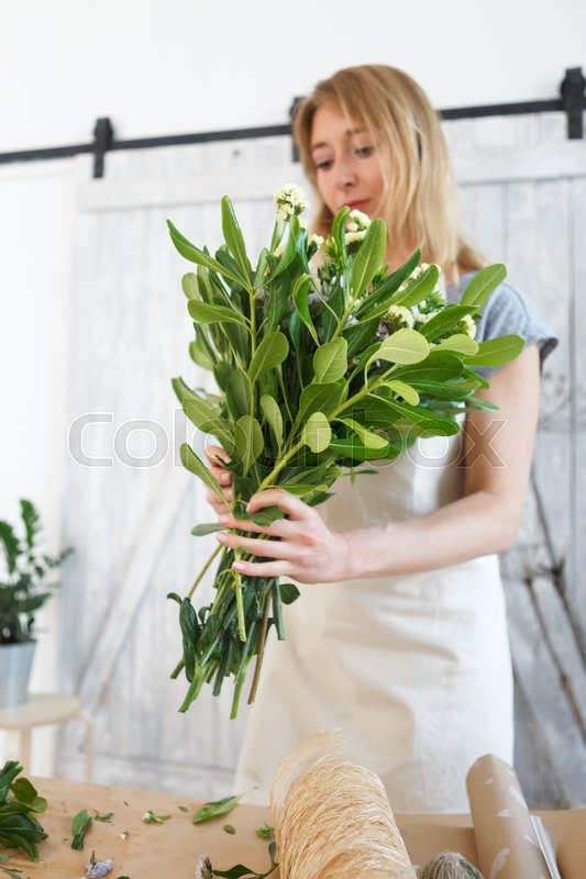 Stock image of 'Florist in apron with bouquet at work in flower shop'