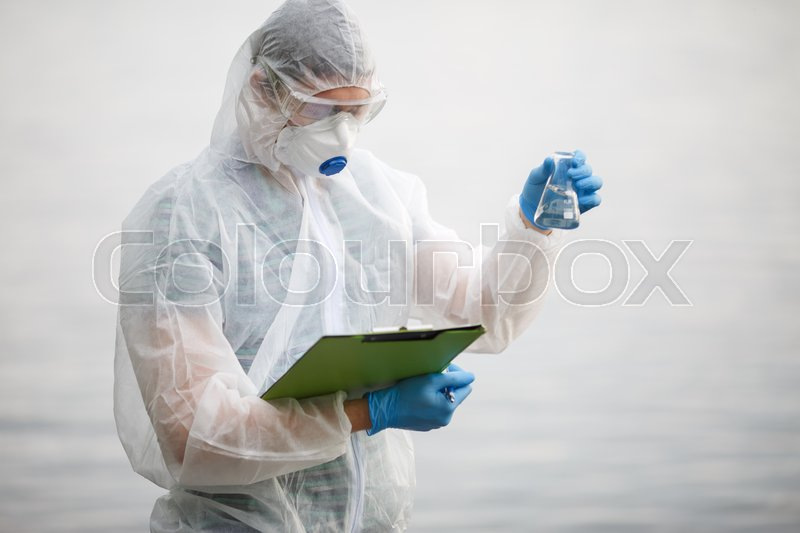Stock image of 'Ecologist with bulb and folder on river bank, blurred background'