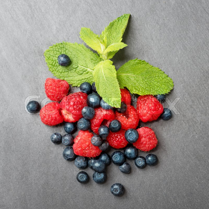 Stock image of 'Fresh washed raspberries, blueberries and mint leaves. Organic berries on grey slate stone board. Top view.'