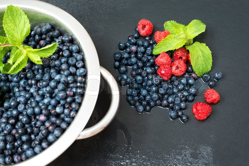 Stock image of 'Fresh washed raspberries, blueberries, mint leaves with waterdrops. Colander with freshly washed organic berries on grey slate stone board.'
