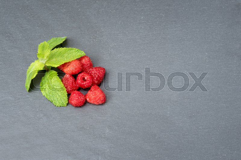 Stock image of 'Fresh washed raspberries and mint leaves. Organic berries on grey slate stone board. Top view, space for text.'