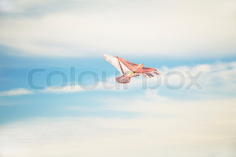 Stock image of 'colorful kite flying high in the sky blue'