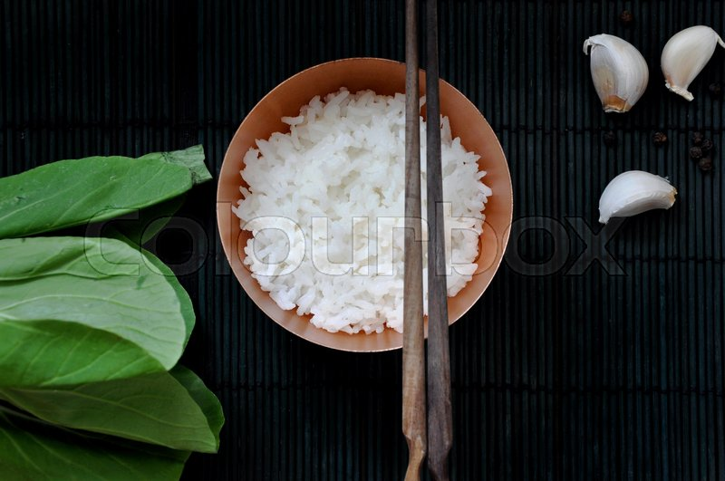 Stock image of 'Top view of white rice bowl with chopstick and ingredients put on black bamboo mat background'