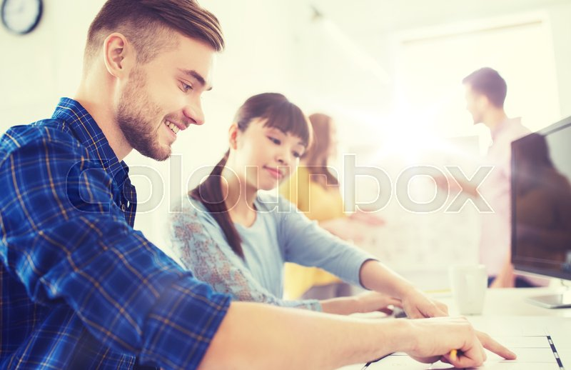Stock image of 'business, startup and people concept - happy creative team with blueprint at office'