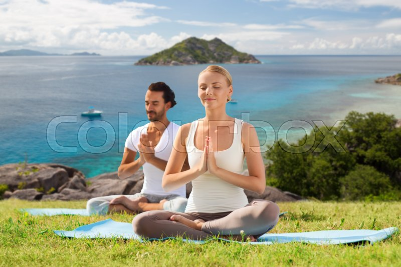 Stock image of 'fitness, sport, meditation and people concept - happy couple doing yoga and meditating outdoors over natural background and sea'