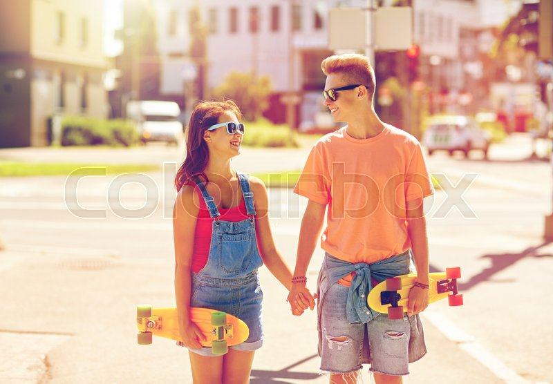 Stock image of 'summer holidays, extreme sport and people concept - happy teenage couple with short modern cruiser skateboards on city street'