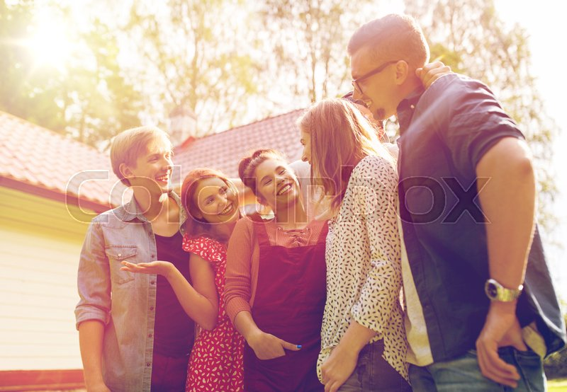 Stock image of 'leisure, holidays, reunion, people and friendship concept - happy teenage friends talking at summer garden'
