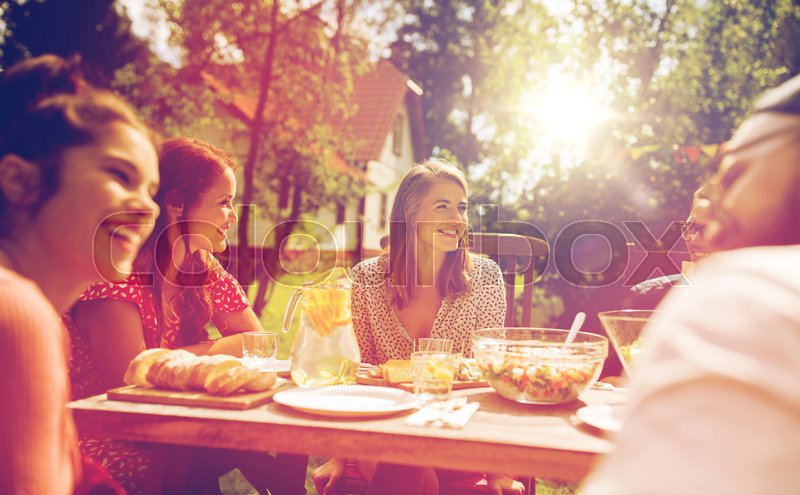 Stock image of 'leisure, holidays, eating, people and food concept - happy friends having dinner at summer garden party'