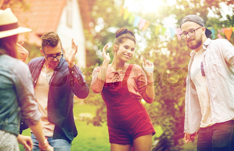 Stock image of 'leisure, holidays, fun and people concept - happy friends dancing at summer party in garden'