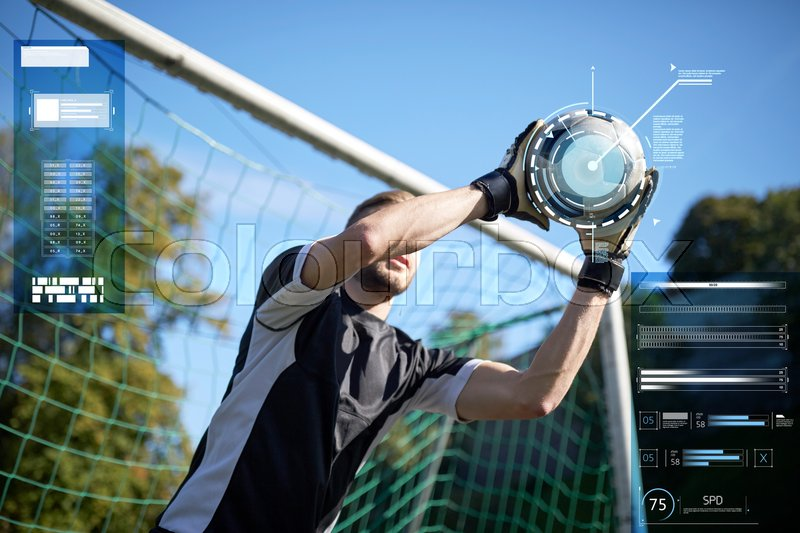 Stock image of 'sport, technology and people concept - soccer player or goalkeeper catching ball at goal on football field'